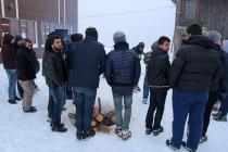 Les locaux se réchauffent autour d'un feu en dansant